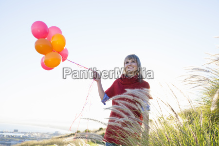 young woman on grassy hill holding
