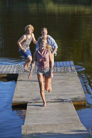 three young adult friends running on