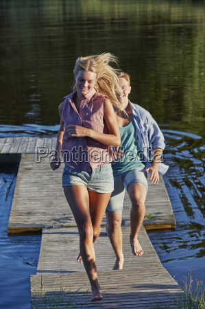 young adult couple running on pier