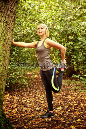 woman stretching legs in woods