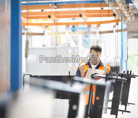 worker inspecting painted parts in sheet