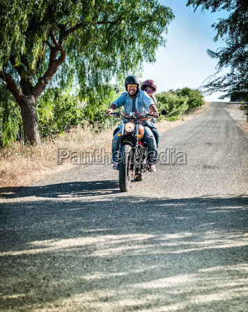 mid adult couple riding motorcycle on