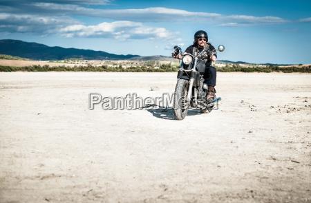 mature man riding motorcycle across arid