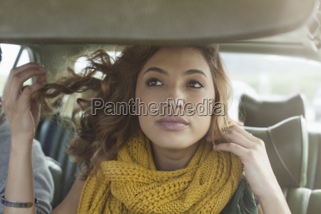 young woman checking herself in car
