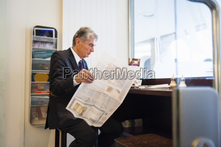 senior businessman reading broadsheet in cafe