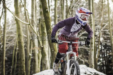 young female mountain biker riding through