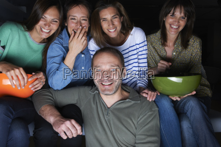five adult friends laughing and watching