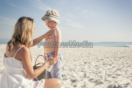 mid adult mother applying sun lotion