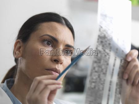 female scientist examining dna gel in