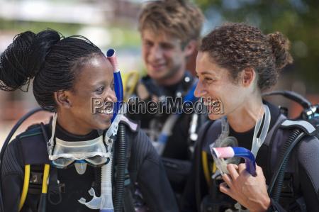 three young adult scuba divers preparing