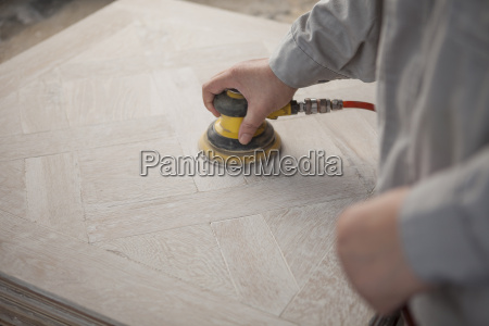 carpenter smoothing surface of wood plank
