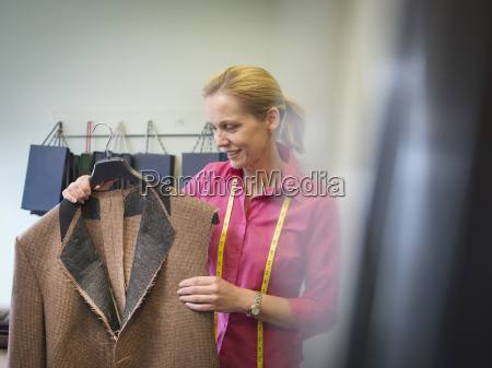 female worker inspecting jacket in clothing