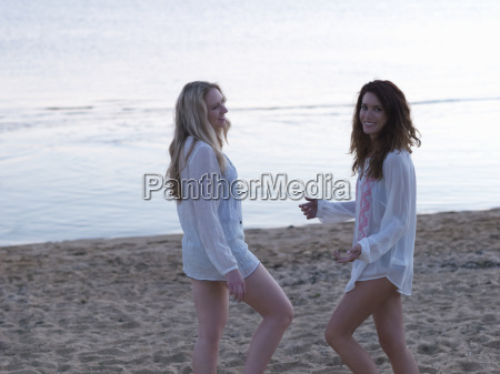 two young women friends standing chatting