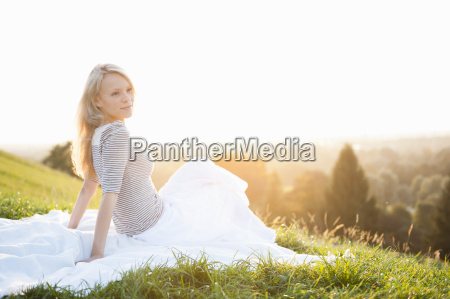 young woman sitting on park hill