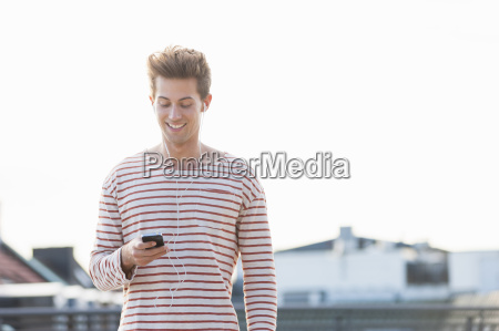 young man on rooftop wearing earphones