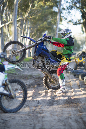 young male motocross racer holding up