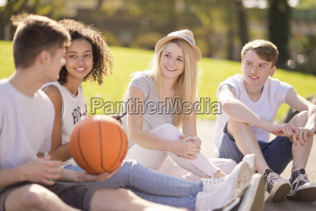 four young adult basketball players sitting