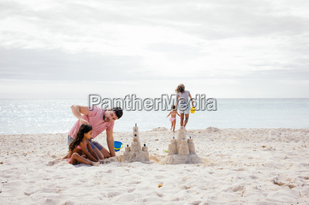 couple and two girls building sandcastle