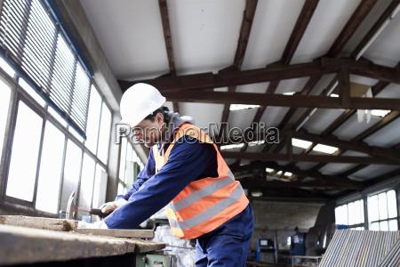 fabrikarbeiter haemmern auf werkbank in betonbewehrungsfabrik