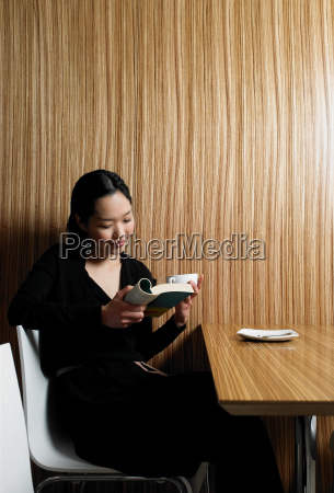 young woman reading book in cafe