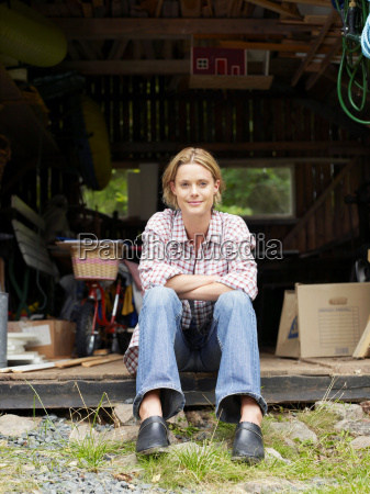 woman sitting in shed smiling
