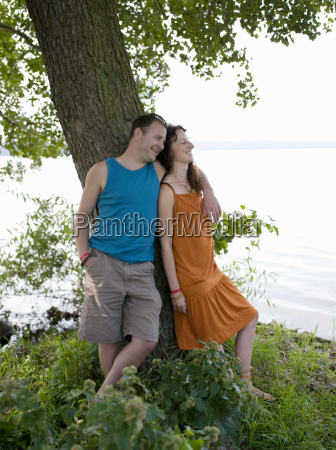 man and woman standing under tree
