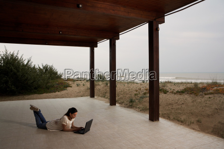young woman using laptop on beach