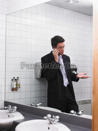 man reflected in office washroom mirror