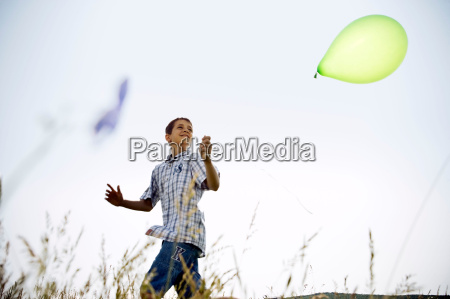 boy running with balloon