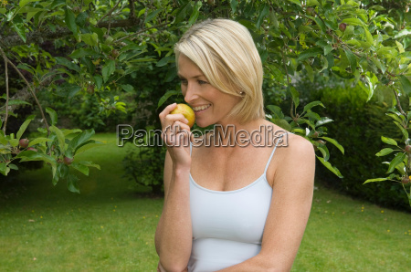 woman in orchard eating apple