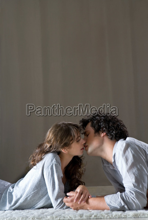 young couple laying on floor kissing