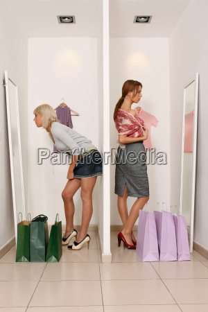 young women looking at shop mirrors