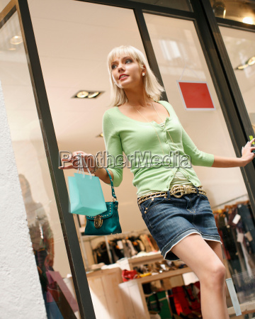 young woman walking out of shop