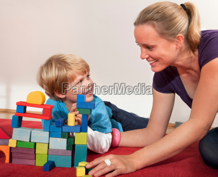 mother and son play with building