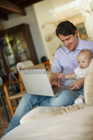 father sitting at laptop with young