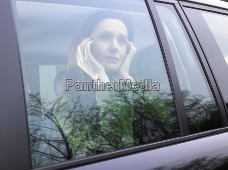 woman looking through her car window
