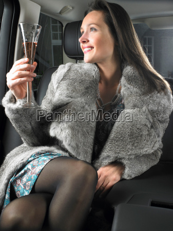 woman in car drinking and celebrating
