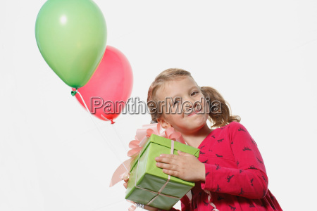 young girl holding present balloons