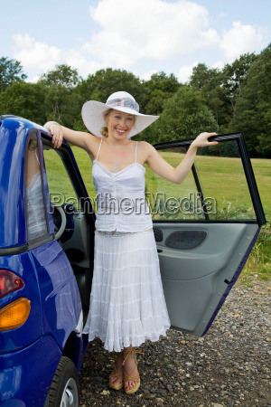 young woman standing by electric car
