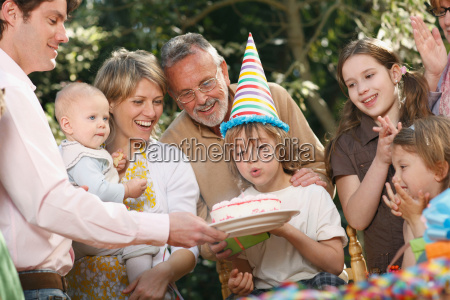 young boy blowing out candles at