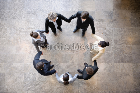 business people holding hands in circle