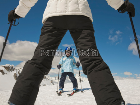 woman teaching boy to ski