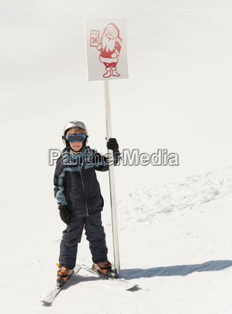boy skier holding santa sign