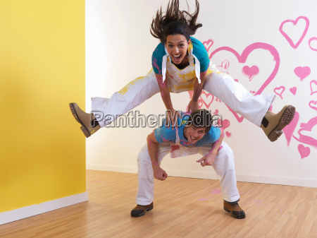 girl leap frogs over man