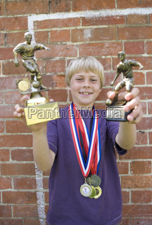 child footballer with medals and trophy