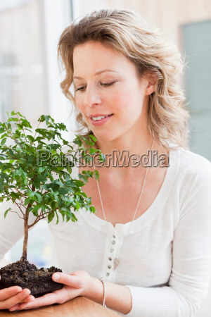woman holding a little tree