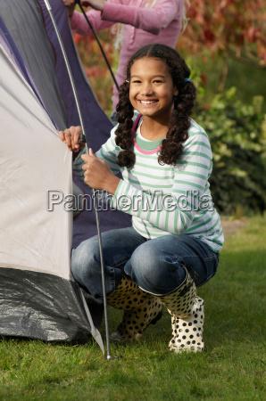 two girls erecting tent
