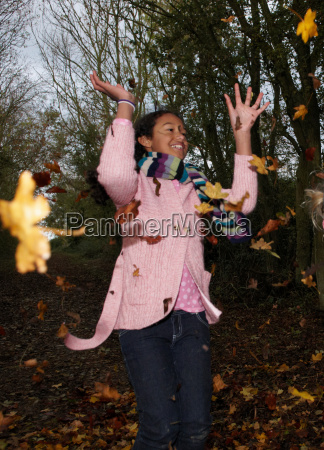girl throwing autumn leaves
