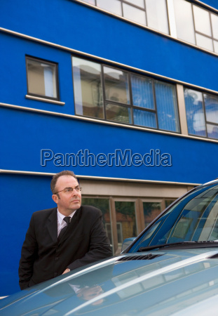 businessman chauffeur leaning on car