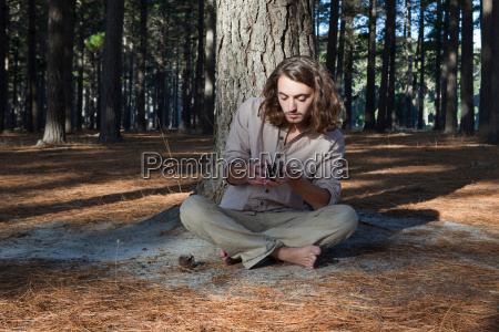 man looking at pine cone